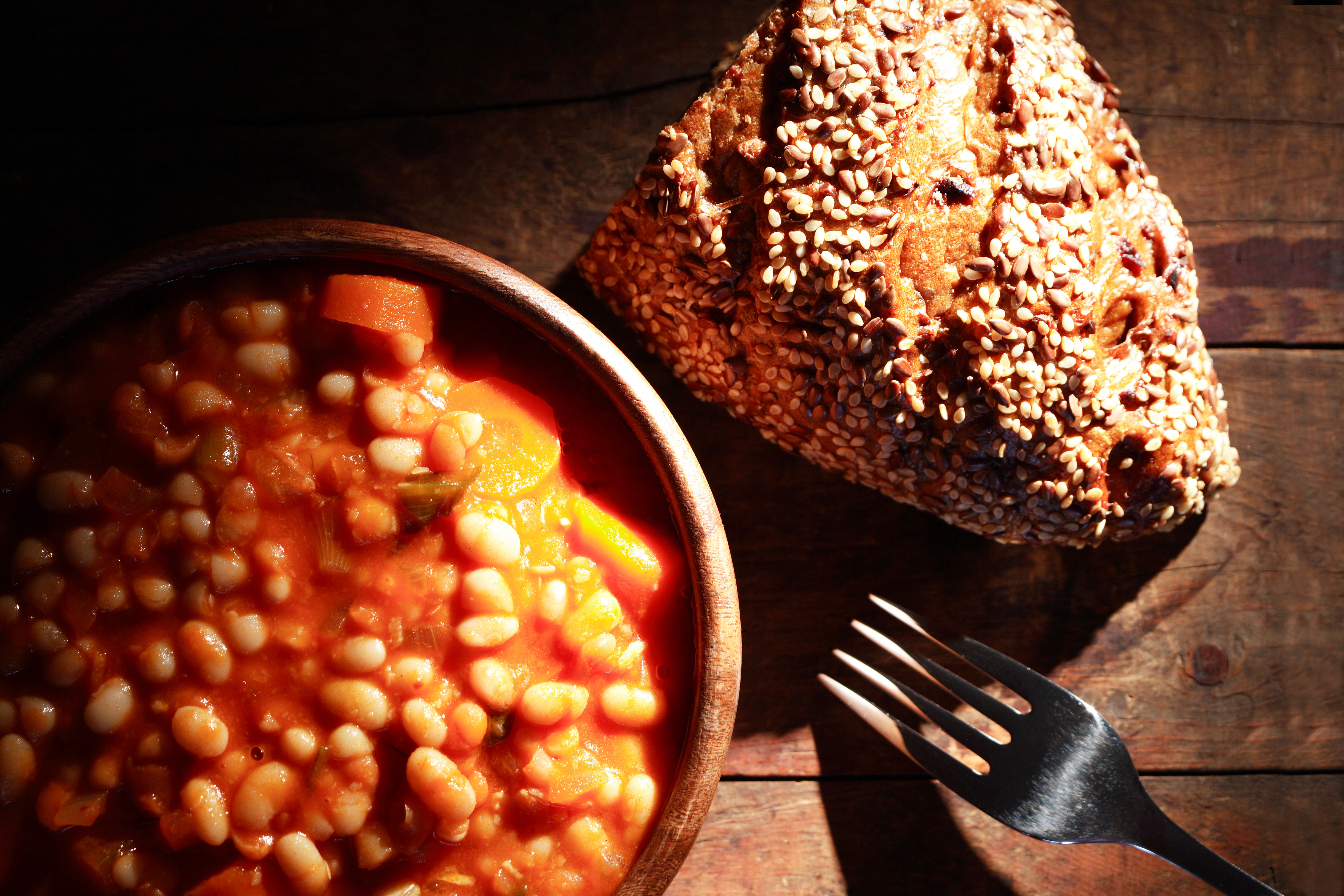 Wooden bowl full of stewed beans near fork and bread